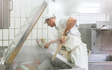 Fleischer kocht Würste im Kessel und stellt so Brühwurst her