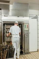 Fleischer bereitet Wurst und Fleisch zum Räuchern vor