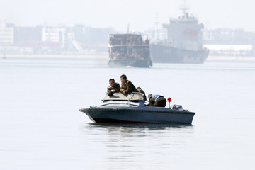 North Korea soldiers lean in a boat on Yalu River, near the North Korean town of Sinuiju, opposite the Chinese border city of Dandong