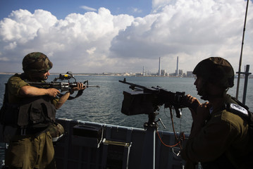 Israeli soldiers stand in position aboard a patrol boat  off Ashdod port