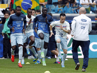 France's players warm up before their international friendly soccer match against Brazil in Porto Alegre
