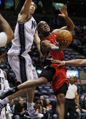 Toronto Raptors' Jarrett Jack goes up for a lay up between New Jersey Nets' Yi Jianlian of China and Jarvis Hayes in East Rutherford