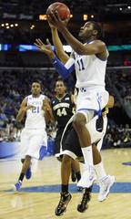 Kentucky guard Wall shoots over Wake Forest defenders during the first half of their 2010 Division I men's NCAA basketball tournament game in New Orleans