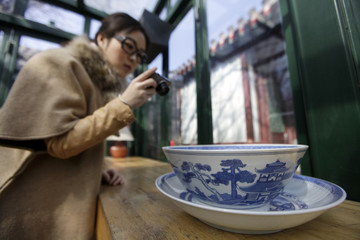 Zhuang Jing takes a picture of a Chinese porcelain in a public living room at a Beijing traditional hotel in central Beijing