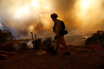 Firefighters protect homes during the Blue Cut Fire in San Bernardino County, California
