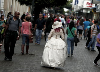 Barahona walks along a central avenue while wearing clothing of the Victorian era in San Jose