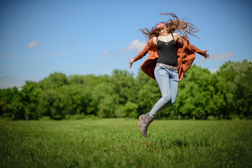 Young woman jumping from joy in the green park on a bright, sunny, summer day, enjoying life and youth