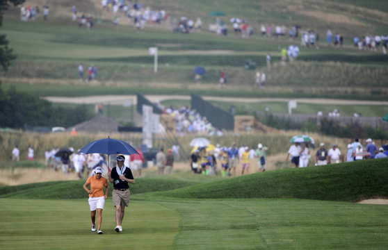 Maria Hernandez of Spain leaves the course with spectators after play was suspended for rain and lightning during the second round of the Women's U.S. Open Golf Championship in Oakmont