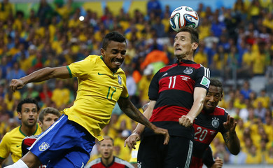Germany's Klose heads the ball beside Brazil's Gustavo during their 2014 World Cup semi-finals at the Mineirao stadium in Belo Horizonte