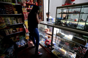 A former rebel who now runs a small marketn store in her house works at the counter in Bogota