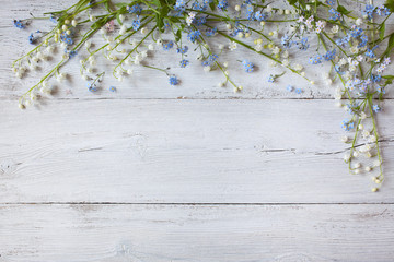 Spring flowers of lilies of the valley, forget me not on a wooden background
