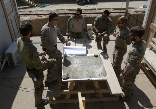 U.S. special forces soldiers discuss beside a map at their base in Helmand