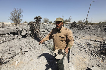 A Palestinian surveys the scene after an Israeli air strike in the Gaza Strip