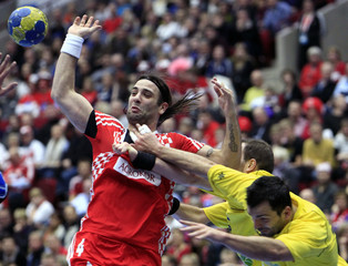 Balic struggles for the ball with Romania's defensive players during their game at the Men's Handball World Championship in Malmo