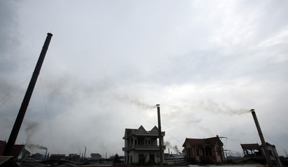 Smoke rises from chimneys of paper factories outside Hanoi