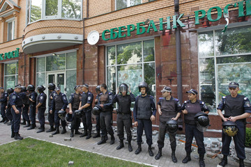 Interior Ministry security force members stand guard outside a branch of Sberbank of Russia bank that was attacked during a pro-Ukrainian anti-separatist rally in Kiev