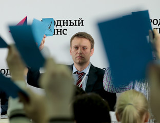 Russian opposition leader Navalny holds his membership card during voting at a congress of the People's Alliance political party in Moscow