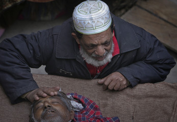 Chaudhry Mohammad Bagh leans down to touch the head of his 62-year-old brother Chaudhry Mohammad Gulab, a heart patient, before his burial in Lahore