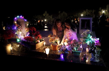 A mother and daughter take part in a vigil at the grave of a loved one at a cemetery in Barva de Heredia