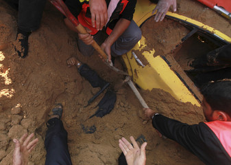 Civil defense members try to dig out a wounded Palestinian man, who is buried under the sand after an Israeli air strike took place near his car, in the northern Gaza Strip