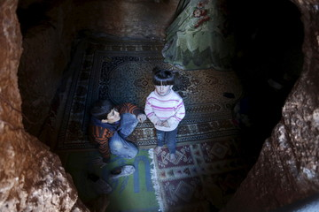 Internally displaced Syrian children stand at the entrance of their makeshift shelter that is an underground cave in Om al-Seer, southern Idlib countryside, Syria