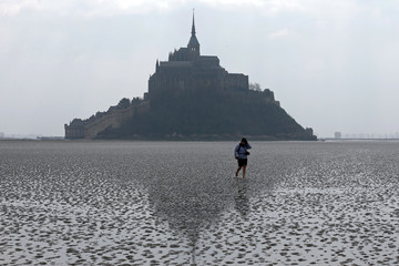 A woman walks on the sand at low tide around the Mont Saint-Michel 11th century abbey off France's Normandy coast