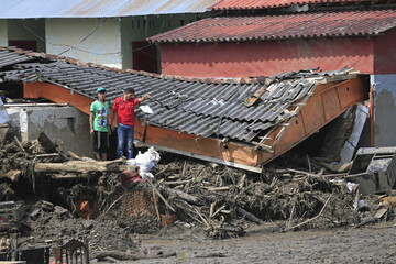 Residents stand in front of damaged houses after a landslide sent mud and water crashing onto homes close to the municipality of Salgar
