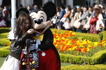 A visitor reacts as she hugs Disney character Mickey Mouse at Tokyo Disneyland in Urayasu