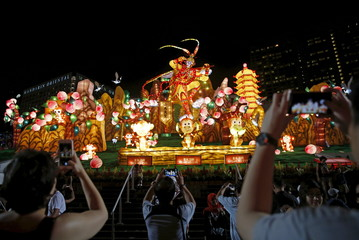 People take photos of a Monkey King lantern during the River Hongbao Lunar New Year celebrations at the Marina Bay floating platform in Singapore