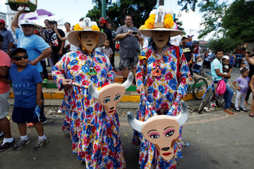 """Two masked dancers pose for a photo during the annual """"Torovenado del Pueblo"""" festival, held in honour of San Jeronimo, the patron saint of the city of Masaya"""