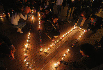 People light candles during a peace vigil in Bogota