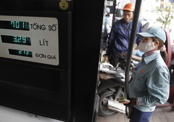 A worker pumps petrol to a motorcycle at a gas station in Hanoi