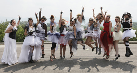 Married women dressed in wedding and fancy dresses pose for a picture during the annual Parade of Brides festival in Krasnoyarsk