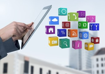 Businessman holding tablet with apps in front of buildings