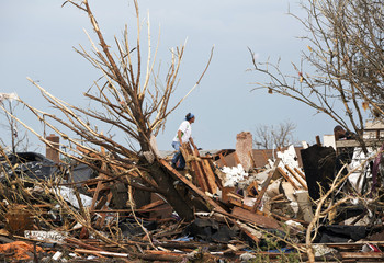 A man looks through the remains of a home after a huge tornado struck Moore, Oklahoma