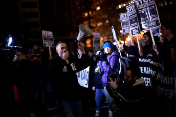 Demonstrators against U.S. president-elect Donald Trump march along the inaugural parade route outside the Trump International Hotel on Pennsylvania Avenue in Washington