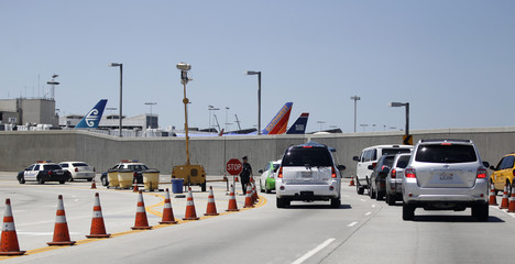 Vehicles wait at a police checkpoint at the entrance to LAX, Los Angeles International Airport, in Los Angeles