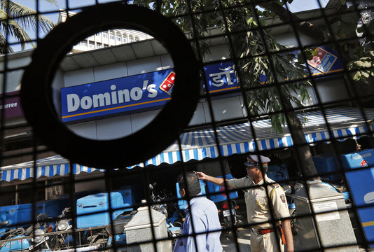 A policeman talks to an employee of a Dominos Pizza outlet after it was ransacked by activists in a Mumbai suburb