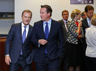 Poland's PM Tusk and Britain's PM Cameron arrive at a group photo during a EU summit in Brussels