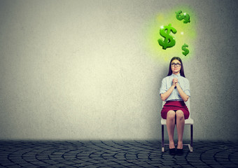business woman sitting on chair with hands clasped praying  looking at dollar symbols above