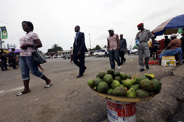 Residents walk past a bowl of tropical fruits for sale on a street near Libreville bus station