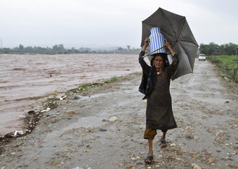 A nomadic woman carries a milk container while shifting her belongings to a safer place from the flooded banks of river Tawi after heavy rains in Jammu