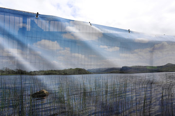 Security fencing covered with scenic pictures of County Fermanagh surrounds an unfinished building site in the village of Irvinestown, Northern Ireland