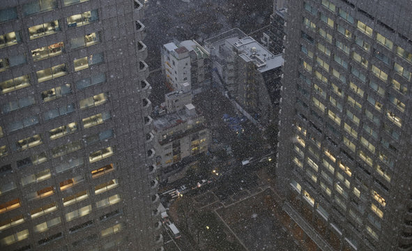 A general view of the business district is seen as snow falls in Tokyo