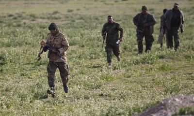 Shi'ite fighters walk with their weapons in the town of al-Alam