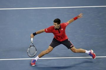 Novak Djokovic of Serbia runs to hit a return against David Ferrer of Spain at the China Open tennis tournament in Beijing