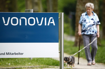 A woman walks her dog next to the logo of German real estate company Vonovia SE in Bochum