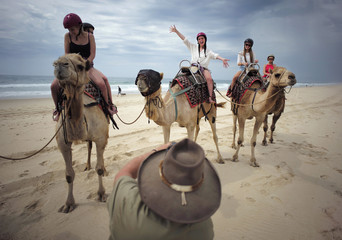 Tourists pose for a picture during a camel safari alongside the Pacific Ocean on Lighthouse Beach