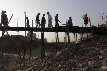 People walk on a bridge made of bamboo to cross a polluted part of Buriganga river in Dhaka