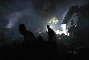 Survivors walk in a blackout caused by a major earthquake in Constitucion